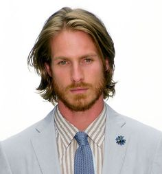 long hair man in suit (lapel pins are a fall must-have for the trendy man who enjoys raiding his gramma's jewelry box)