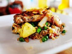 grilled pork chops on top of pineapple fried rice