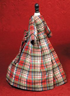 """ANTIQUE PLAID COTTON FRENCH FASHION DRESS. 4 ½"""" shoulder width; 14"""" length. Fine plaid fabric made up in gown featuring bodice with tiny gathers at the fitted waist band with long ties edged in black velvet then arranged in large bow with streamers at waist back, inset long sleeves with velvet-trimmed cuffs, self-piping at neckline, back yoke with two-button closing, box-pleated full skirt, silk lining. Commentary: Antique frock designed in youthful style, excellent condition. Est.$200-$300"""