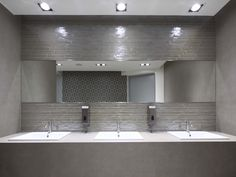 With the staggered laying and two different colors, this area creates a perfect synergy between intimate wellness and functional space.  #glass #mosaics #wall #bathroom #public #space #grey #shiny #light #nice #cool
