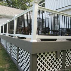 A soft gray toned, capped composite deck is beautifully 'framed' with white rails and black metal balusters. To polish off the project, the under deck was finished with white lattice 'framed' in gray. | houzz.com
