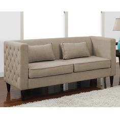 This sofa is sure to add style and grace to any living space with its striking tufted detailing on the outside of the arms. This contemporary sofa also offers a light tan upholstery and includes two rectangular pillows to complete the look.