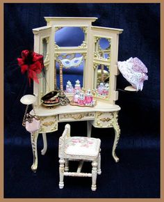 Museum Quality Ladies Dressing table and Stool. Hand made from wood finished in cream with a transparent gold glaze giving it an aged look. This Beautifully Shaped Table has fixed Mirrors and a central opening drawer with contents {fixed} On top of the dresser we have A tray of Swarovski crystal perfume bottles A jewellery box with jewels A masquerade mask on a stand There are two hats on the arms and a silk purse.
