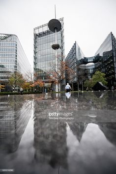 Low angle view of commuters walking in the More London business district on a wet day, London, UK.