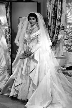 Costume designer Helen Rose created the wedding dress that Elizabeth Taylor wore when she starred as Kay Banks in Father of the Bride in The gown that Taylor later wore at her wedding to Conrad Hilton was noticeably similar in design. Movie Wedding Dresses, Famous Wedding Dresses, Celebrity Wedding Dresses, Wedding Movies, Wedding Dress Pictures, Celebrity Weddings, Wedding Gowns, Iconic Dresses, Elizabeth Taylor