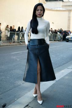"""A #turtleneck paired with a below-the-knee skirt? Your first thought might be """"mom gear!"""", but this showgoer adds some youthful #drama with a slit and sleek white pumps."""