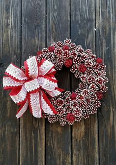 Red and white painted and flocked pine cone wreath with red and white lace bow.  Dozens of pine cones were used to create this elegant Christmas