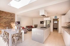 Single-storey kitchen extension in Hampton, designed and built by L&E (Lofts and Extensions) - don't move extend! White Kitchen, Kitchen Extension, Bi-Fold Doors, Kitchen Design Ideas, Exposed Brickwork, Metal Dining Chairs, Integral Wine rack, Skylight