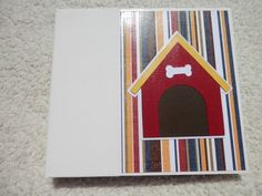 This is a 6x6 inch chipboard album that any dog lover would enjoy. The spine of the album is white and the patterned papers used in the album include colors of dark red, blue, yellow, and brown. The papers have prints of dog related phrases and and images. This album has 14 pages and 15 photo mats. Album includes machine sewn pockets inside for you to add even more pictures or memorabilia. This album is adorned with ribbons and dog themed embellishments on every page. Cover can be…