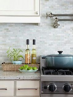 Light & Livable: Backsplash  Less dressy than glass but with a high-gloss finish, the glazed clay backsplash tiles were installed in a running bond pattern along the range wall. The arrangement is reminiscent of a mosaic, but it ends up looking more timeless. The pale, light-reflective hue of the tiles helps to visually expand the narrow kitchen.