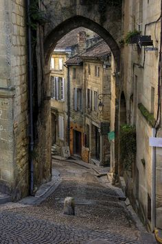 old cobblestone street with a shop around the bend (st emilion town)
