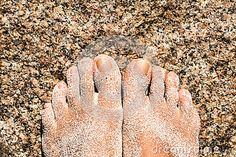 Female foots on a rock with specks of sand on them