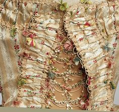 Detail front view, robe à la francaise, probably Great Britain, 1775-1780. Cream and pale salmon striped silk embroidered with floral garlands, fly fringe.