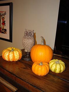 Halloween decor, mini pumpkins and gourds with an owl statue