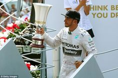 Mercedes star Hamilton lifts his trophy after triumphing at the Italian Grand Prix at Monz...
