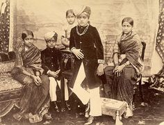 The Maharaja of Mysore's Chldrrn. The elder princesseswear very traditionalbelted sarees with woven checks this time. The littlest girl's costume is not really visible, butit is different fromher sisters.Thiswas taken soon after the Maharaja's death from diptheria, leaving their mother as Regent untilten-year-oldKrishnaraja IVcame of age. He ruled Mysore until 1940, highly praised for the cultural and technological advancements of his state.