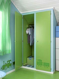 Dette gutterommet har fått friske farger, grønt i kombinasjon med blått. Fra garderobeskapdørene og bortover veggen tøffer et grønt lokomotiv.