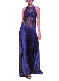 This enthralling navy gown by Sougat Paul available at strandofsilk.com is sure make you sizzle like an absolute diva. The halter style gown features a sheer intricate floral cutwork bodice and a backless design. The bodice is adorned with all over delicate beads that add richness to the ensemble. The flowing flared satin skirt of the gown lends a further zeal and charisma. Wear it for an evening do with a classic elegant hairdo and high heels! #navy #gown #halter #diva #sheer #satin…
