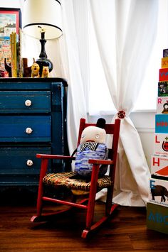 from apartment therapy - love the blue dresser, red rocker... would be great for the boys room down the line