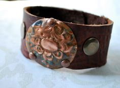 Rusted Patina Floral Medallion with Rivets in Two Tone Kodiak Leather Cuff by Bandana Girl Copper medallion is textured and blue with rust patina added...riveted with copper rivets to a great medium / dark brown kodiak leather. Antique brass snap to secure. Soft and supple leather feels great on. All metal and leather work is done by hand here in my studio! Original Designs by Melinda Orr All jewelry will come gift boxed.Â