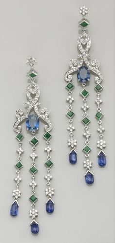 A pair of sapphire, kyanite, emerald, diamond and eighteen karat white gold earrings each dangle earring centering an oval-shaped sapphire, within a scroll of diamond-set round brilliant-cut diamonds, suspending fringes of collet-set square-cut emeralds, round brilliant-cut diamonds, and briolette-cut kyanites