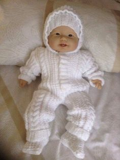 An Aran cable / Irish Knit all in one suit with attached hood plus a hat and socks made in a soft white baby yarn. It buttons down the front. Will fit 0-3 month baby or a 22 inch Reborn Baby Doll Just right for keeping baby warm in this adorable outfit / pram set Easy wear and