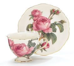 """Romantic Rose teacup and saucer. Cream colored porcelain with a lovely rose design. Holds 8 oz. and trimmed 14K gold includes 1 cup and 1 matching saucer in a blue gift box. 3 1/4""""H X 3 1/4""""Diameter."""
