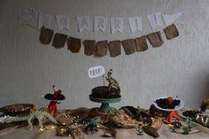 Mesa de festa infantil com decoração de dinossauros e   bolo de brigadeiro com morango