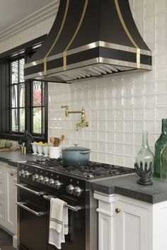 Walker Zanger tiles on the backsplash. Drew's honeymoon house kitchen with AGA black range and hood Kitchen Tiles, Kitchen Dining, Kitchen Cabinets, Kitchen Stove, Property Brothers Kitchen, Hgtv Kitchens, Spanish Home Decor, White Tile Backsplash, Cocinas Kitchen