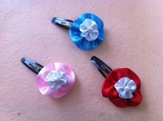 You can turn any ordinary hair clip into something fancyby adding on a flower. This ribbon flower is a fine example and very easy to put together. You make 2 circular flowers, stack them, then add on a bead.    Materials   blue ribbon white ribbon hair clips beads thread needle scissors fabric glue