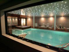 La piscine intérieure par l'esprit piscine - Piscine 10 x 5 m Revêtement blanc Escalier droit sur la largeur Margelles et plage en teck