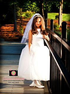 Gorgeous lighting on a bridge with black railings really helps her stunning white dress for her FIrst Holy COmmunion stand out.