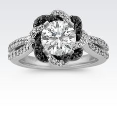 A lovely braided twist of black sapphires and round diamonds create a unique halo for the center 1.00 carat diamond of your choice. This shimmering engagement ring, as part of our exclusive Noire collection, is crafted of quality 14 karat white gold and is embellished by 46 round diamonds (approx. .46 carat TW) and by 16 round black sapphires (approx. .20 carat TW) set above a black rhodium finish. The total gem weight of this setting is approximately .66 carat.