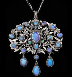 ARTHUR (1862-1928) & GEORGINA GASKIN (1866-1934)  An Arts & Crafts silver pendant, of florets and leaves, set with opals and with  three opal drops