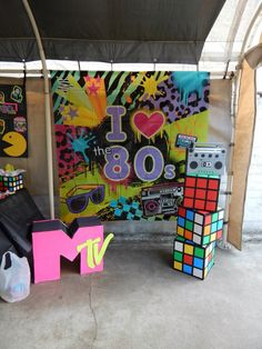 All 80's props made using Dollar Tree products and cardboard boxes. For the Rubiks cubes, Cut poster boards into squares and tape them on box with double sided tape. Do not glue - it makes the poster board crinkle. Take the black electrical tape and run it between each square. Also covered a box with silver duct tape and drew tuner and knobs to make the boom box.