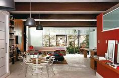 Pilares e vigas de aço dispensam o uso de paredes e integram as áreas nesta casa na zona sul carioca. Os tijolos originais das paredes foram descascados e o piso tem peças de demolição que se unem ao cimento queimado. A estante de peroba-mica e painel de pinho-de-riga com sobras de madeira (RF Marcenaria). Em contraponto aos acabamentos neutros, as divisórias de alvenaria que fecham o banheiro e a mureta da cozinha receberam tinta acrílica vermelho-pitanga (Sherwin-Williams).