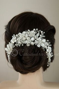 This bridal headpiece is stunning and unique. Silver frosted flower with rhinestone jewel centers are surrounded by ivory pearls, rhinestones, seed beads and crystal beads. There is a clip in the cent