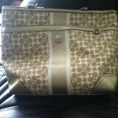 2011 summer coach bag Gold and white with an easy to clean leather exterior. Lots of pockets and the interior is great except for the stain at the bottom of the interrupt. Get lots of compliments! I wouldn't get rid of it if my husband wasn't making me in order to clean the closets lol Coach Bags