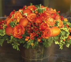 This composition combines femma roses, ranunculus, orange chincherinchee,  hypernicum berries, three different types of geranium foliage, red rose  hips, Mandarin oranges and nectarines in an antique copper bucket