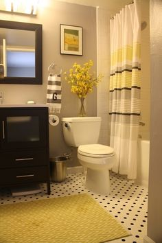 Grey walls, espresso vanity, yellow accents in this lovely bathroom.