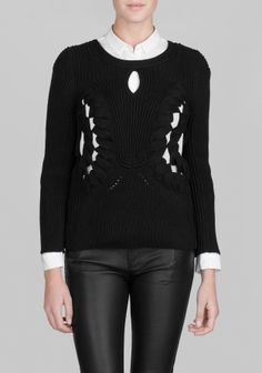 A cotton sweater featuring chunky knit patterns and breezy openings in the front and back.