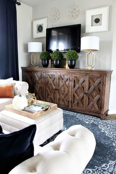 A modern family room loft featuring beautiful burnt orange pillows, blue wool rug, brass lamps, agate wall art, & wall decor from Homegoods {sponsored}