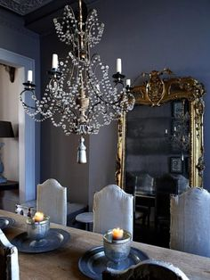 Gold mirrors, dark walls. Chandelier.