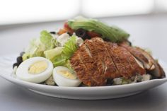 Classic Cobb Salad with chicken, blue cheese, bacon, tomatoes, egg, sprouts, avocado, black olives, hearts of romaine tossed with lemon Dijon red wine vinaigrette