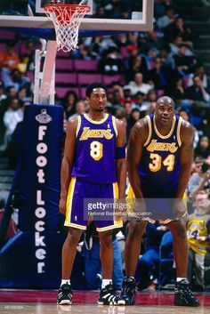Shaquille O'Neal #32 and Kobe Bryant #8 of the Los Angeles Lakers look on against the New Jersey Nets on April 2, 1998 at Continental Airlines Arena in East Rutherford, New Jersey.