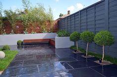 aménagement jardin sans entretien - clôtures en bois, parterres surélevés, dallage gris et déco en arbres d'ornement