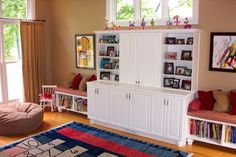 Link to lots of playroom ideas with pictures, low book shelves and kid's chair in this photo