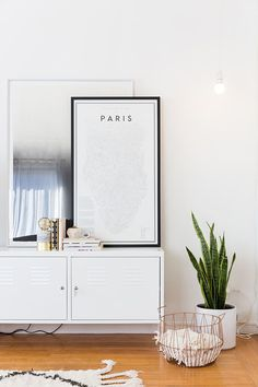 Minimalist inspired living space with a floating shelf, a framed map of Paris, and an indoor plant