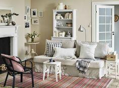 Obývací pokoj s béžovou rozkládací pohovkou, vysokou skříní a bílou stoličkou využitou jako stolek.