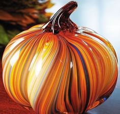 This gorgeous art glass pumpkin features a swirled design in orange, yellow, and blue. These are sold individually and make a terrific addition to your fall decorations.